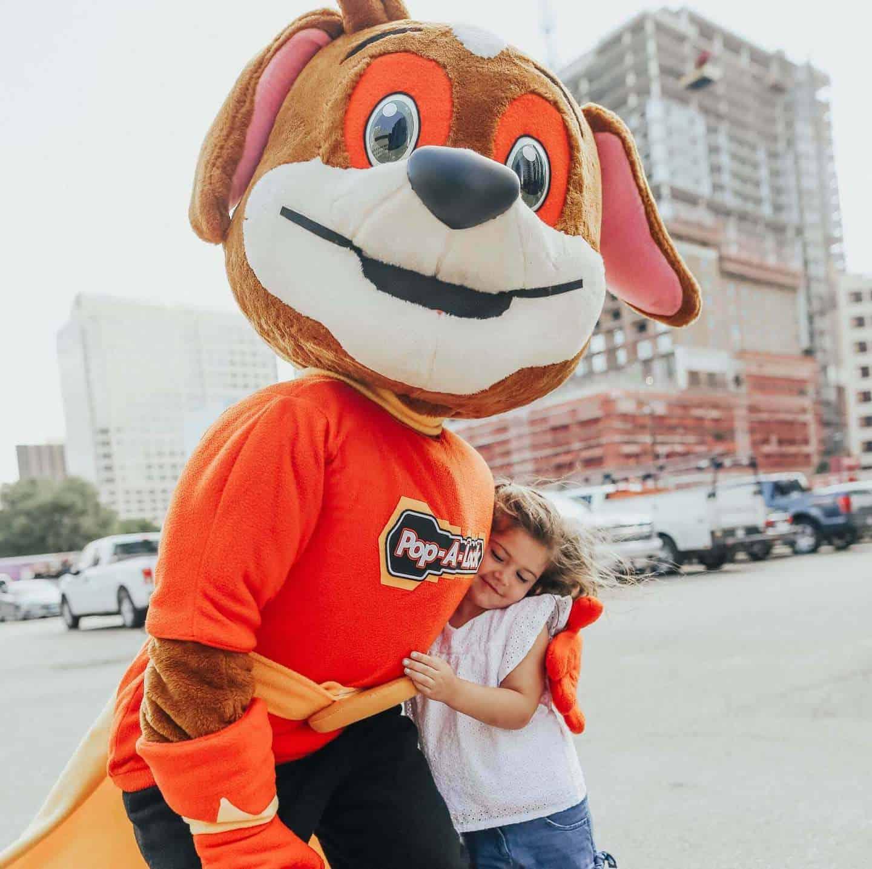 Pop-A-Lock Mascot Hugging Child