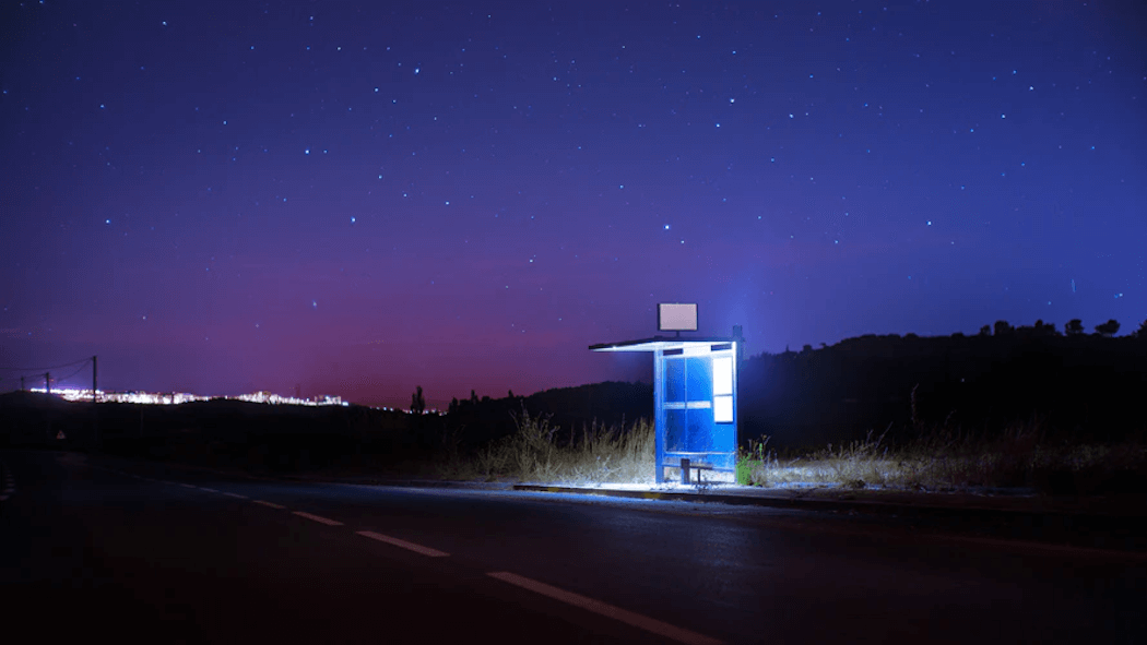 A lit bus stop next to the road at night.
