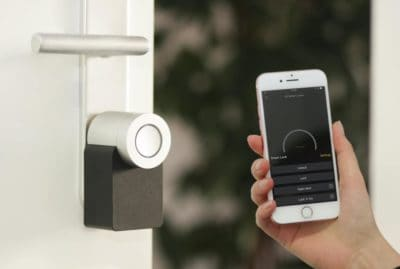 Hand holding a phone up to a smart lock.